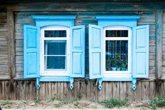 Två åldrades fönstret av ett gammalt trähus i Ryssland Arkivbild