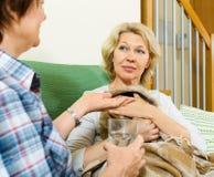 Två åldrades kvinnor med preventivpilleren och exponeringsglas av vatten Arkivfoton