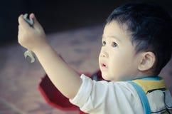 Två år barn som rymmer en skiftnyckel Arkivfoto