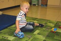 Två år barnpojkelek med bilar Bildande leksaker för förträningen och dagisbarnet, inomhus lekplats, livsstilbegrepp royaltyfri fotografi