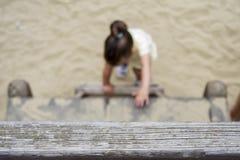 Två år gammal flickaklättring på stegen arkivfoto