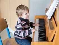 Två år leka piano för gammal litet barnpojke Royaltyfri Bild