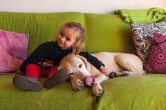 Två årig flicka och labradorsammanträde i en soffa hemma Arkivfoto