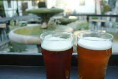 Två öl/ölcloseup, med springbrunnen i bakgrund Arkivfoto