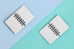 Två öppna pappers- anteckningsböcker på en diagonal kulör backround Lekmanna- sikt för bästa lägenhet med blå grön past arkivbilder