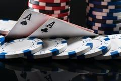 Två överdängare av att spela kort ligger på chiper för att spela poker på en mörk bakgrund Arkivfoton