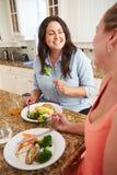 Två överviktiga kvinnor bantar på äta sunt mål i kök Fotografering för Bildbyråer