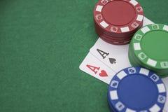 Två Ace av poker bredvid massor av chiper Arkivfoto