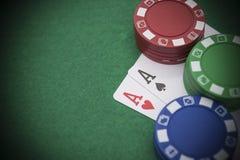 Två Ace av poker bredvid massor av chiper Royaltyfri Bild
