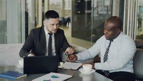 Två affärskollegor som diskuterar deras affärsavtal och ser notepaden i stilfullt kafé Afrikansk amerikan stock video