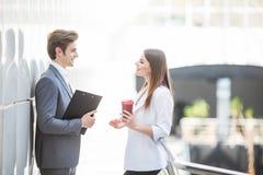 Två affärskollegor som i regeringsställning står korridoren som har informell diskussion med kaffe Royaltyfri Foto
