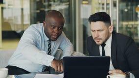 Två affärskollegor som ser bärbar datordatoren och diskuterar deras projekt i modernt kontor med glasväggar stock video