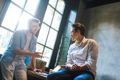 Två affärskollegor som sitter på en tabell och att ha ett möte arkivbild