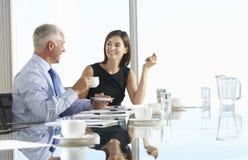 Två affärskollegor som sitter runt om styrelsetabellen som in har Arkivfoton