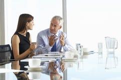 Två affärskollegor som sitter runt om styrelsetabellen som har informell diskussion royaltyfri fotografi