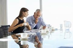 Två affärskollegor som sitter runt om styrelsetabellen som har informell diskussion Arkivbild