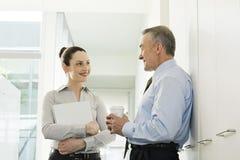 Två affärskollegor som talar i korridor arkivbilder