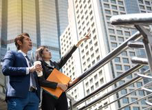 Två affärskollegor som utomhus står på kontorsbyggnad Arkivbild