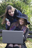 Två affärskvinnor i parkera som köper en bärbar dator Arkivbild