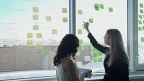 Två affärskvinnor på bakgrund av fönstret i korridor diskuterar ämnen arkivfilmer