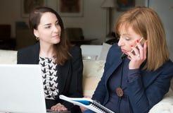 Två affärskvinnor som arbetar det hemmastadda kontoret arkivbilder