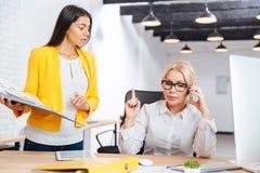 Två affärskvinnor som diskuterar idéer på tabellen i kontoret Arkivbilder