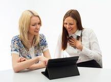 Två affärskvinnor som i regeringsställning möter med minnestavlaPC Fotografering för Bildbyråer