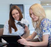 Två affärskvinnor som i regeringsställning möter med minnestavlaPC Arkivbild