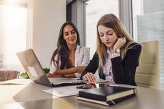 Två affärskvinnor som läser dokument genom att använda minnestavladatorsammanträde på skrivbordet i modernt kontor arkivfoton