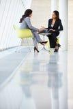 Två affärskvinnor som omkring möter, bordlägger i modernt kontor Royaltyfri Fotografi