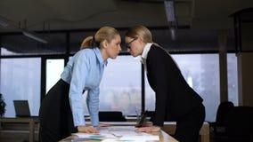 Två affärskvinnor som ser med utmaningen på de, konkurrens på arbete arkivfilmer