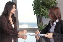 Två affärskvinnor som sitter på kontorsskrivbordet Arkivbild