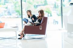 Två affärskvinnor som sitter på läs- mappar för soffa och har c royaltyfri fotografi