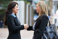 Två affärskvinnor som skakar händer utanför kontor Arkivfoto