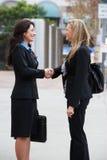 Två affärskvinnor som skakar händer utanför kontor Royaltyfri Bild
