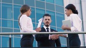 Två affärskvinnor som talar på terrassen, när en affärsman kommer upp till dem som ska hälsas och talas till dem lager videofilmer