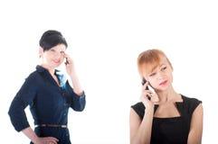 Två affärskvinnor som talar vid mobiltelefoner Fotografering för Bildbyråer