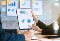 Två affärsledare som analyserar datapapper på en skrivplatta på mötesrum royaltyfri fotografi