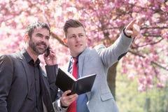 Två affärsmän i parkera med boken och telefonen royaltyfria bilder