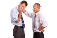 Två affärsmän i skjortor som besväras, en som tröstar som tröstar a Royaltyfria Bilder