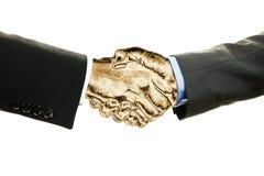 Två affärsmän med guld- skaka händer som isoleras på vit bakgrund Affärs-, teamwork- och finansbegrepp royaltyfri fotografi
