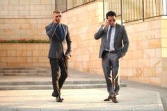 Två affärsmän med mobiltelefoner, nära väggen, Sungl Royaltyfri Foto