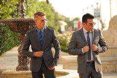 Två affärsmän Near vattenspringbrunnen, solglasögon Fotografering för Bildbyråer