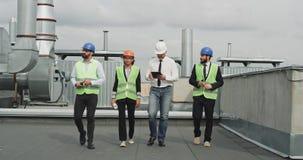 Två affärsmän och ung tekniker med arkitekten som analyserar planet av konstruktionsplatsen och använder en minnestavla dem lager videofilmer