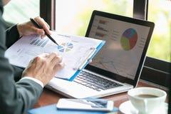 Två affärsmän som analyserar finansiella data för statistik på PCbärbara datorn, po arkivfoto
