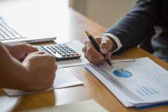 Två affärsmän som analyserar finansiella data för statistik på PCbärbara datorn, po royaltyfri fotografi