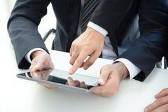 Två affärsmän som använder minnestavladatoren med en rörande skärm för hand Royaltyfria Bilder