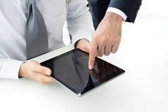 Två affärsmän som använder minnestavladatoren med en rörande skärm för hand Royaltyfri Fotografi