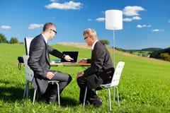Två affärsmän som arbetar i natur royaltyfri foto