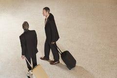 Två affärsmän som drar resväskor i lobby Arkivfoto
